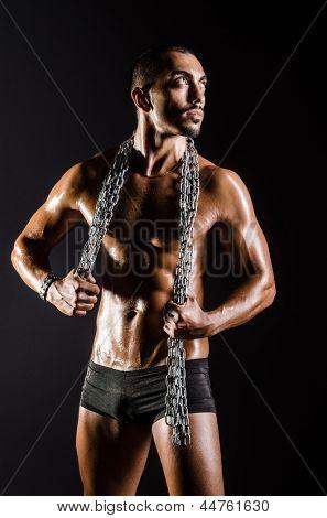 Homem musculoso com cadeia em fundo preto