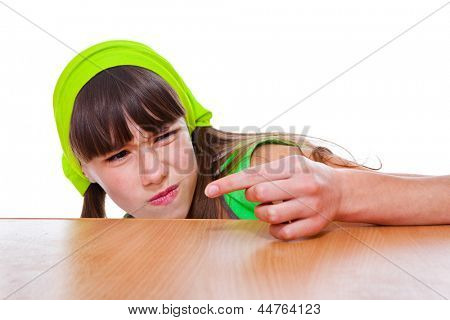 Teenage girl looking at dust on her finger with disgust