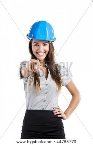 Beautiful and confident young female architect wearing a blue helmet and pointing, isolated on white