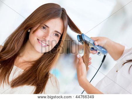 Stylist using a hair straightener on a woman at the salon