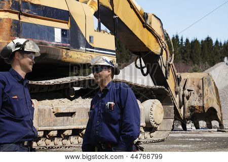 two site workers with giant bulldozer in the background