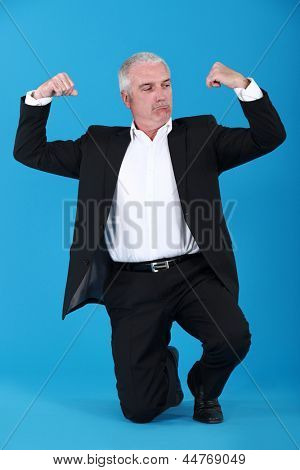 Mature businessman flewing his muscles