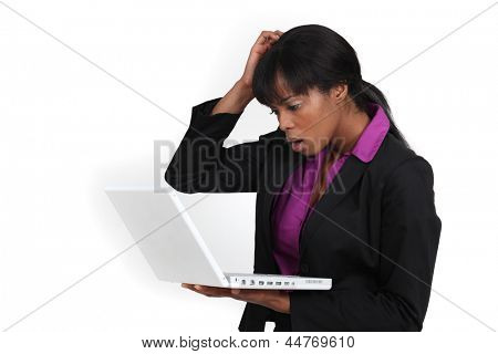An African American businesswoman looking at her laptop with a dubious expression.