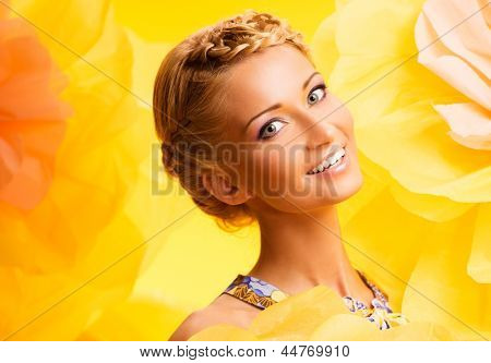 Beautiful young cheerful blond woman in colourful dress among big yellow flowers