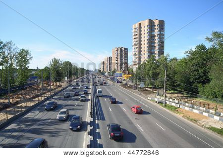 Many cars goes on wide road in large city in sunny summer day. Work is underway to expand prospect.