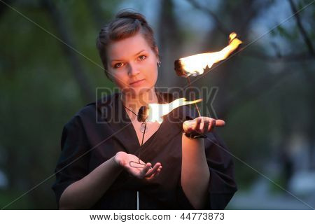 A girl in a black dress shows a fire show on nature.