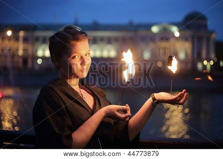 A girl in a black dress shows a fire show in the night near the river.