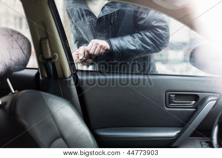 Inside view of it as a man breaks into a car.