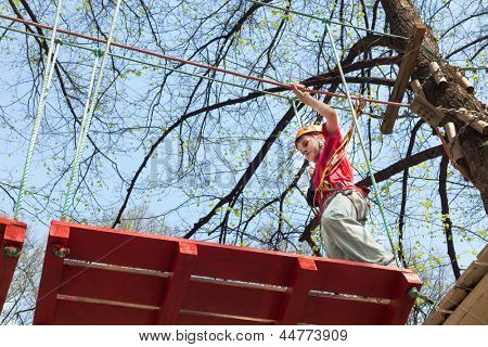 Young climber going to go on a suspension bridge on high ropes course.