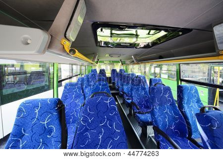 Rows of soft blue seats inside saloon of empty city bus with skylight.