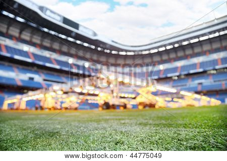 Lawn and lighting system for growing grass at empty outdoor football stadium. Focus on grass.