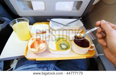 Breakfast in plane (fruit, small bun, juice and tea). Passenger tries tea by teaspoon.
