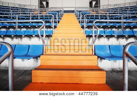Orange ladder and blue grandstand at large football stadium.