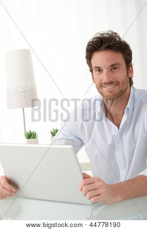 Portrait of happy man sitting at home with laptop computer, smiling at camera.