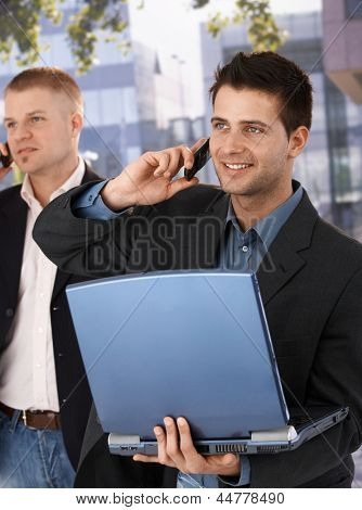 Businessmen using mobile phone, smiling, standing outside of office with laptop computer.