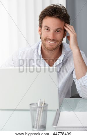 Happy businessman at office desk, using laptop computer, smiling at camera.
