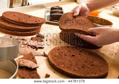 Chef cutting chocolate cake layers and stacking them