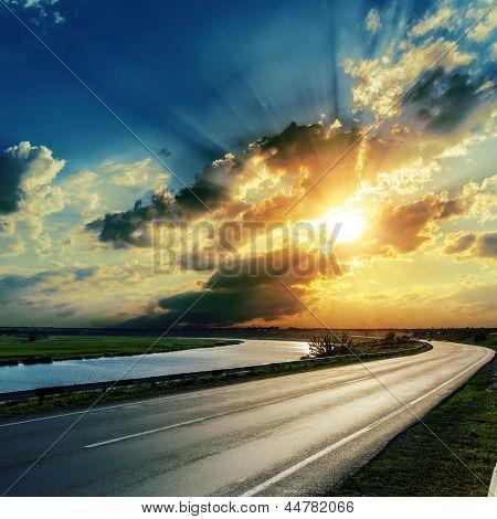 sunset over asphalt road and river