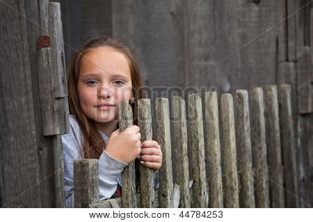 Teengirl standing near vintage rural fence