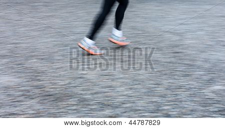 Motion blurred runner's feet in a city environment (panning technique used -> motion blurred image; color toned image)