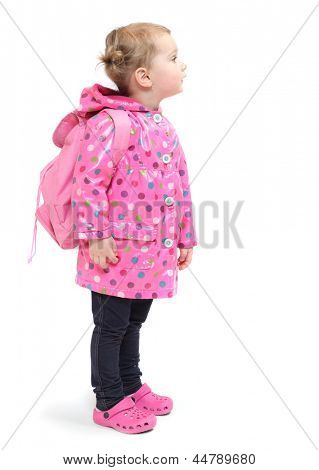 Little girl in the raincoat with backpack going to school.