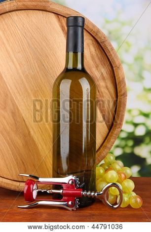 Composition of corkscrew and bottle of wine, grape, wooden barrel  on wooden table on bright background