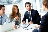 stock photo of interview  - Image of business partners discussing documents and ideas at meeting - JPG