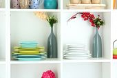 stock photo of armoire  - Beautiful white shelves with tableware and decor - JPG