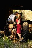 young couple in retro clothing kissing on tractor