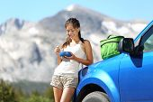 Car road trip woman driver eating lunch break outdoors in mountain landscape in Yosemite National Pa