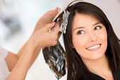 stock photo of brunette  - Brunette woman dying her hair at the beauty salon - JPG