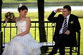 stock photo of coy  - Newlywed couple sat on park bench smiling groom and coy bride with bouquet. ** Note: Slight blurriness, best at smaller sizes - JPG