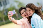 Happy friends taking a self portrait with a cell phone