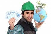 Laborer holding a globe, a green plant and twenty Euros bills