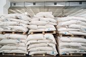 pic of sugar industry  - Rows of big white sacks at large warehouse in modern factory - JPG