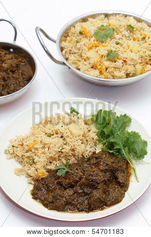 Methi gosht or fenugreek lamb, served with tomato (thakkali) biryani and a leafy salad, with a kadai of the rice behind