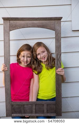 Twin sister girls posing with aged wooden border frame on white wall