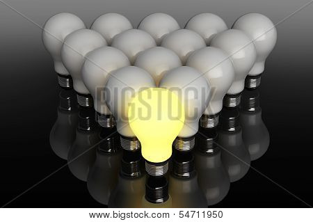 Leadership Concept. One Glowing Light Bulb Standing In Front Of Unlit
