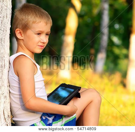 Boy Child Playing With Tablet Pc Outdoor With Forest On Background Game Dependence And New Technolog
