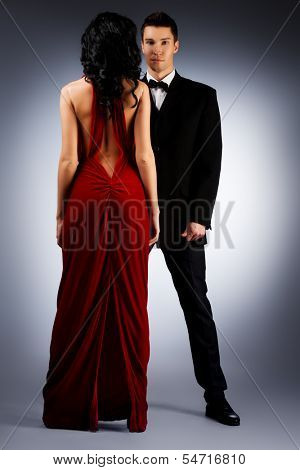 Beautiful young couple in love in evening dresses posing at studio.