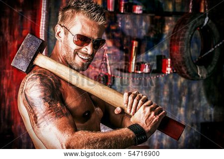 Handsome muscular man with sledgehammer working in the old garage.