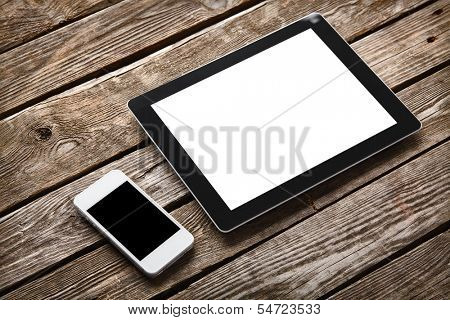 Digital tablet computer and white smart phone with isolated screens on old wooden desk.