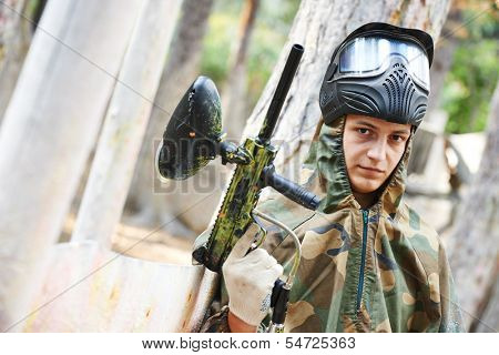 Brave paintball sport player man in protective camouflage uniform and mask with marker gun outdoors