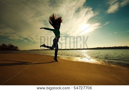 Woman Jumping On The Beach On Sunny Sky Background, Freedom And Health Concept
