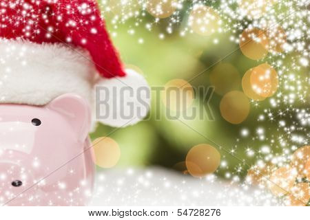 Pink Piggy Bank Wearing Red and White Santa Hat on Snowflakes with Abstract Green and Golden Snow and Light Background - Room for Your Own Text.