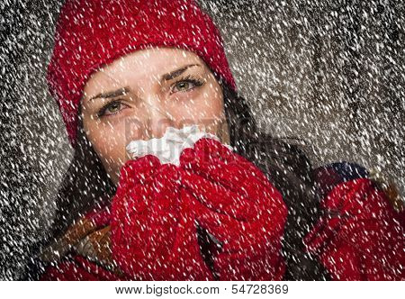 Sick Mixed Race Woman Wearing Winter Hat and Gloves Blowing Her Sore Nose with a Tissue in The Snow.