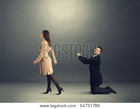 sad man bending the knee before outgoing woman in dark room