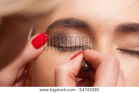 Close up view of the eye of a young female model having eye makeup applied by a beautician