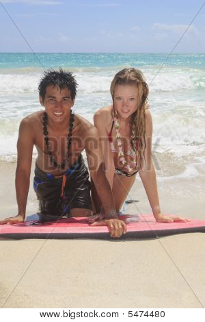Couple Kneeling On A Foam Surfboard At The Beach In Hawaii