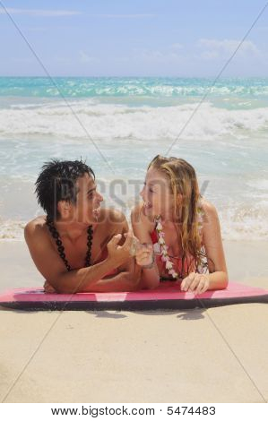 Couple Lying On A Foam Surfboard At The Beach In Hawaii